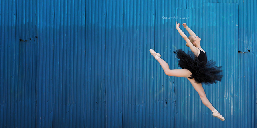 ballerina jumps by blue wall