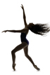Ballerina poses in studio with a silhouette with hair thrown back