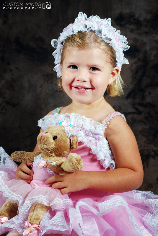 child poses with teddy bear