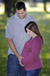 husband and wife in the park holding belly