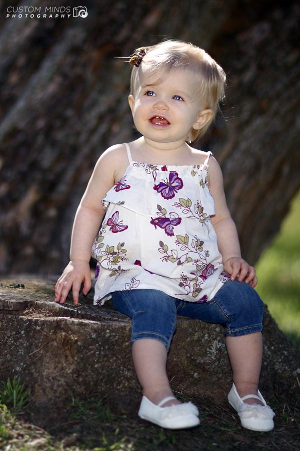 child sitting on a stump
