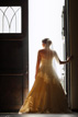 Light floods past a bride in the doorway at Briscoe Manor in Richmond Texas
