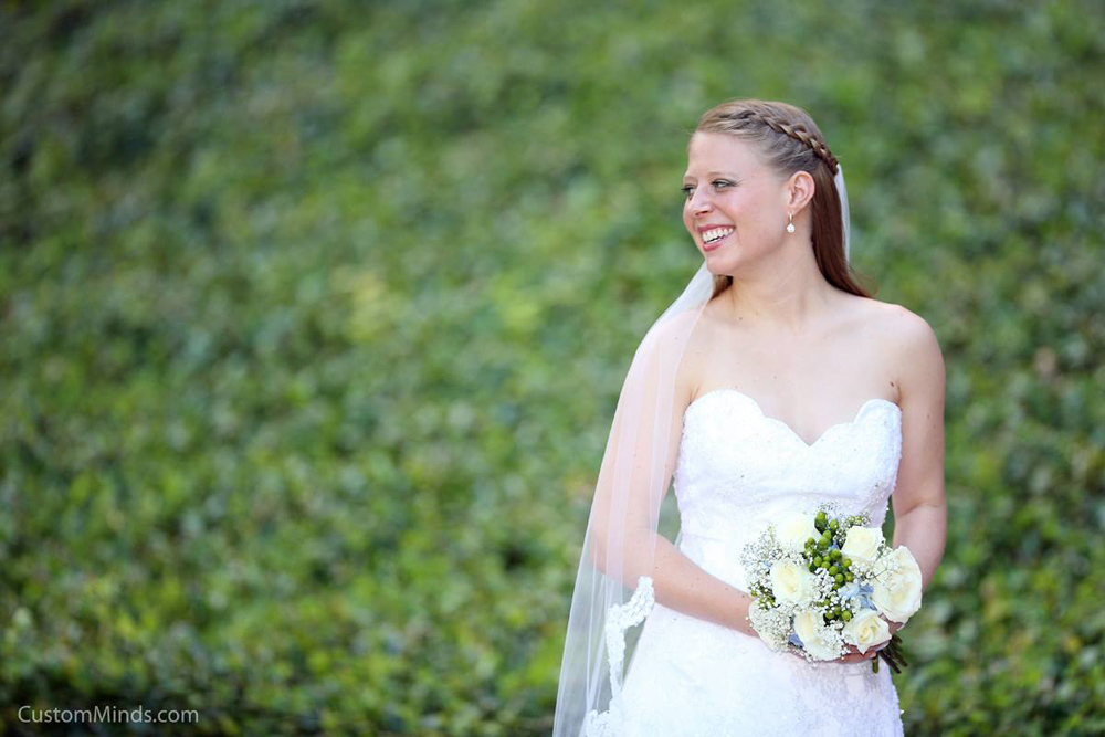 Bride posing by a patch of greenery by the Houston Grand Opera.