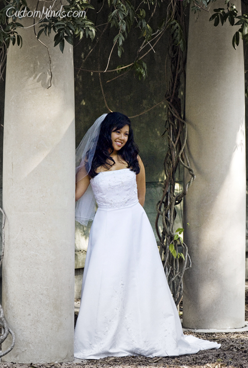 Smiling bride standing by pillars at Hermann Park in Houston Texas