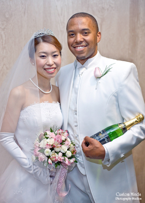 Bride and Groom with champagne and a bouquet.