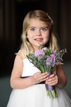 Flowergirl smile and holds flowers in Houston Texas