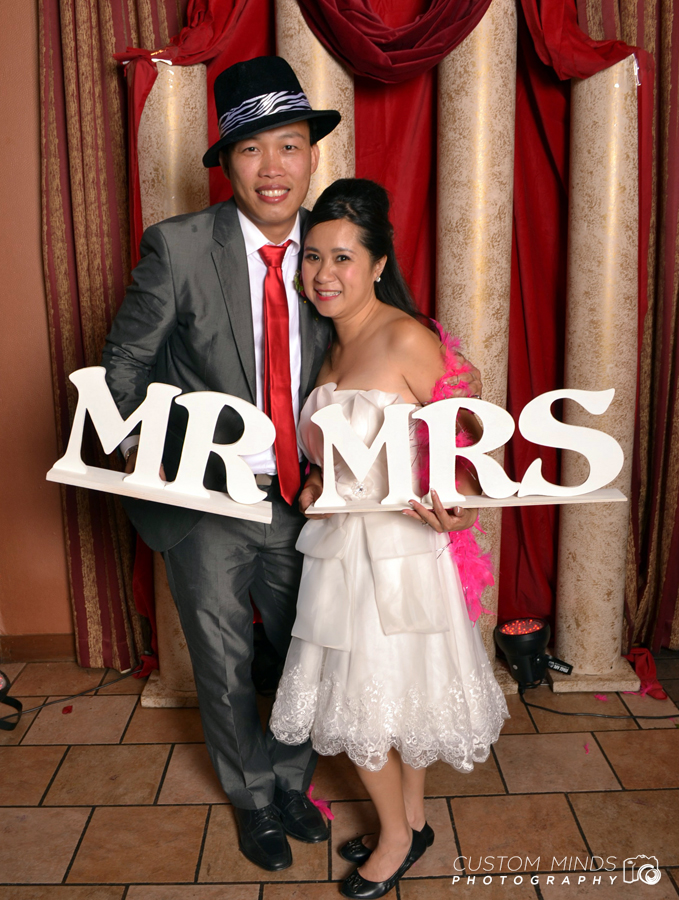 Bride and Groom pose at the wedding photo booth ner Bellaire and the Beltway