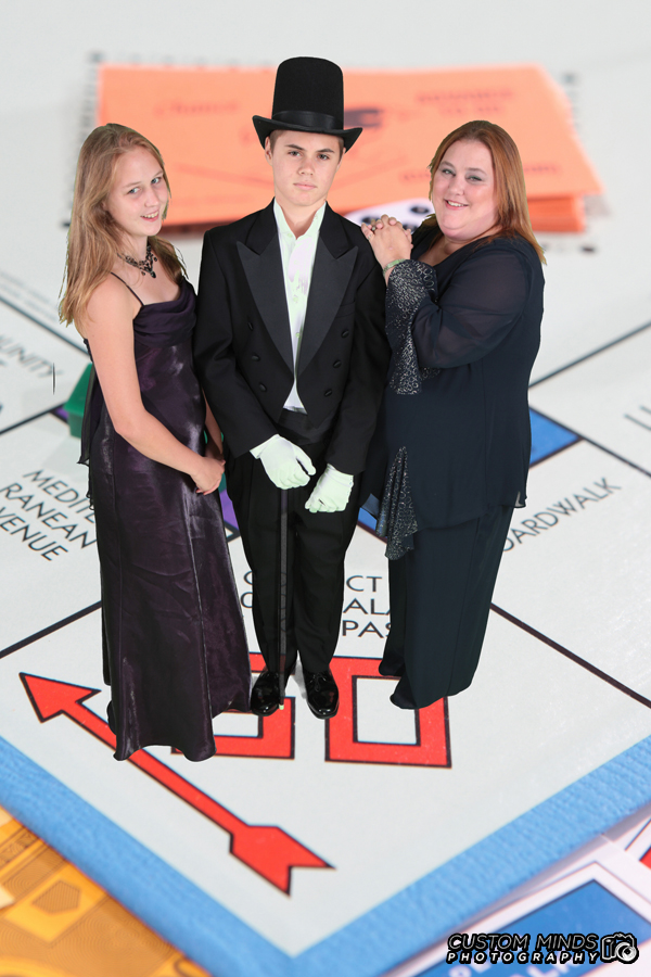 Mother and children pose on a greenscreen Monopoly board for our photo booth