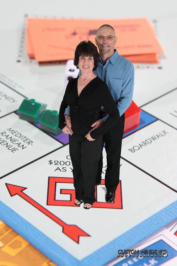 Happy couple smiles while standing on a Monopoly board - Greenscreen photo booth